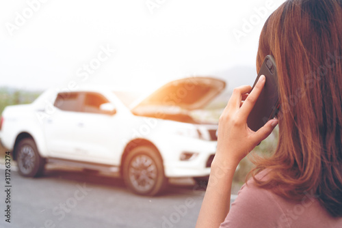 Fotografía Young woman using mobile phone while looking at broken down car