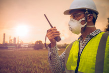 Young Engineers Are Talking Radio Communication And Wearing A White Helmet And PM2.5 Dust Mask, A Beautiful Petrochemical Plant Background, Close Up Engineers Working On A Building Site.