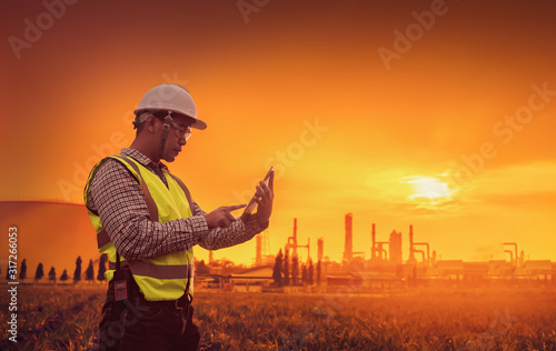 Fototapeta Close-up engineers working in building sites that have tablets, Concept of new plan, white helmet and red radio, Engineering and petrochemical plants - Imagen, PPE conditions in oil and gas refineries obraz