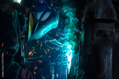Photo Side view of welder in protective helmet welding metal detail with sparks at fac