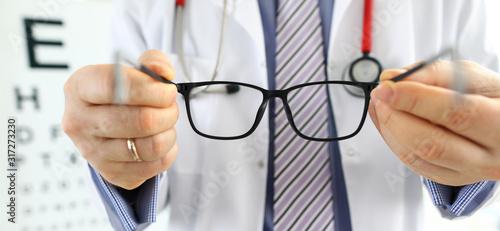 Fotografía Male medicine doctor hands giving pair of black glasses
