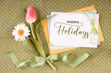 Greeting Card With Caption Happy Holidays On Stack Of Paper Cards Decorated With Springtime Flowers, Daisy And Tulip, And Ribbons With Bow On Olive Green Table Cloth With Polka Dots