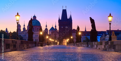 Leinwand Poster Charles Bridge at dawn, silhouette of Bridge Tower and saint sculptures with str