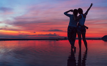 Two Girlfriends Hugging Up And Enjoying A Rose/pink Sunset Sky On The Sea Beach On The Samui Island,Thailand. Calm Warm Countries Vacation Concept Image.