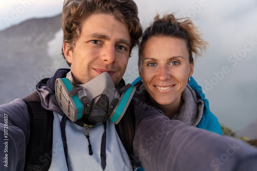 Fotografía Selfie photo of adventure seekers with  beautiful mountain  landscape and blue lake with smoke  in a Kawah Ijen volcano