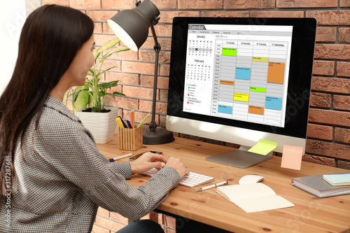 Obraz Young woman using calendar app on computer in office - fototapety do salonu