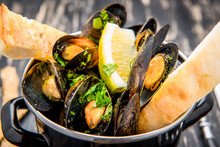 Mussels In Metal Cooking Dish And French Baguette With Herbs