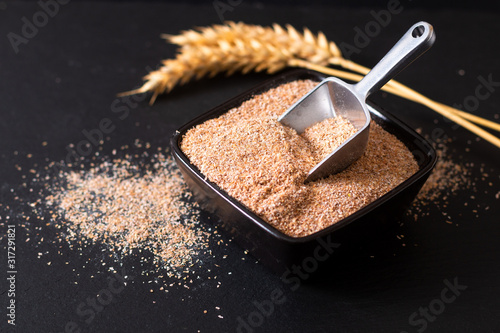 Healthy food concept Organic Wheat bran in black ceramic cup with wheat ear on b Tapéta, Fotótapéta