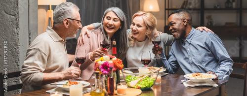 Fototapeta panoramic shot of smiling multicultural friends hugging and holding wine glasses during dinner obraz