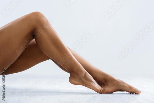 Fotografía Attractive legs of african woman over grey background