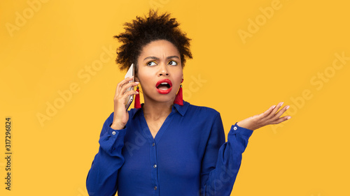 Upset young afro woman talking on mobile phone Canvas Print