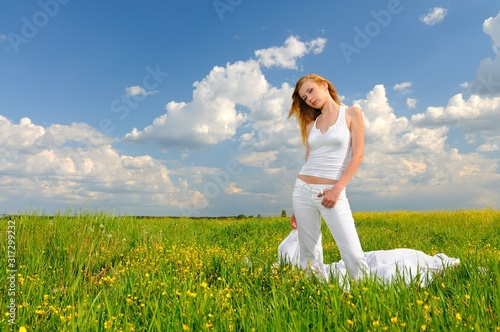 Woman posing in a green field with airiness silk Wallpaper Mural