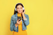 canvas print picture - Young woman listening to audiobook on yellow background. Space for text