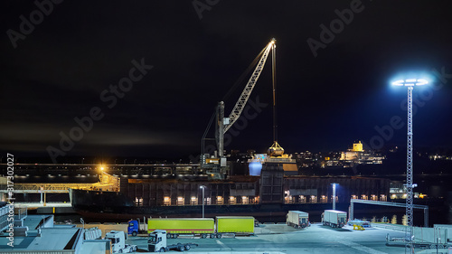 Vászonkép mechanical hydraulic clamshell grabbers loading coal on ship at night