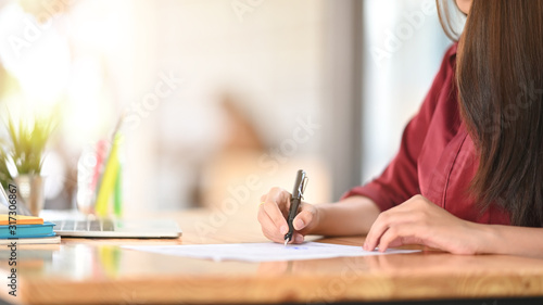 Side shot of woman red shirt while writing on the paper and sitting at the wooden working desk Canvas