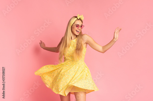 Fototapeta Cheerful woman dancing over pink studio wall obraz