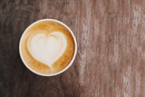 Paper cup of cappuccino coffee with latte art in the shape of heart on wooden background.
