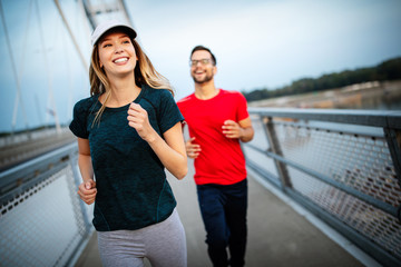 FototapetaBeautiful couple running in nature living healthy