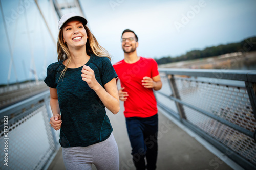 Beautiful couple running in nature living healthy - 317311221