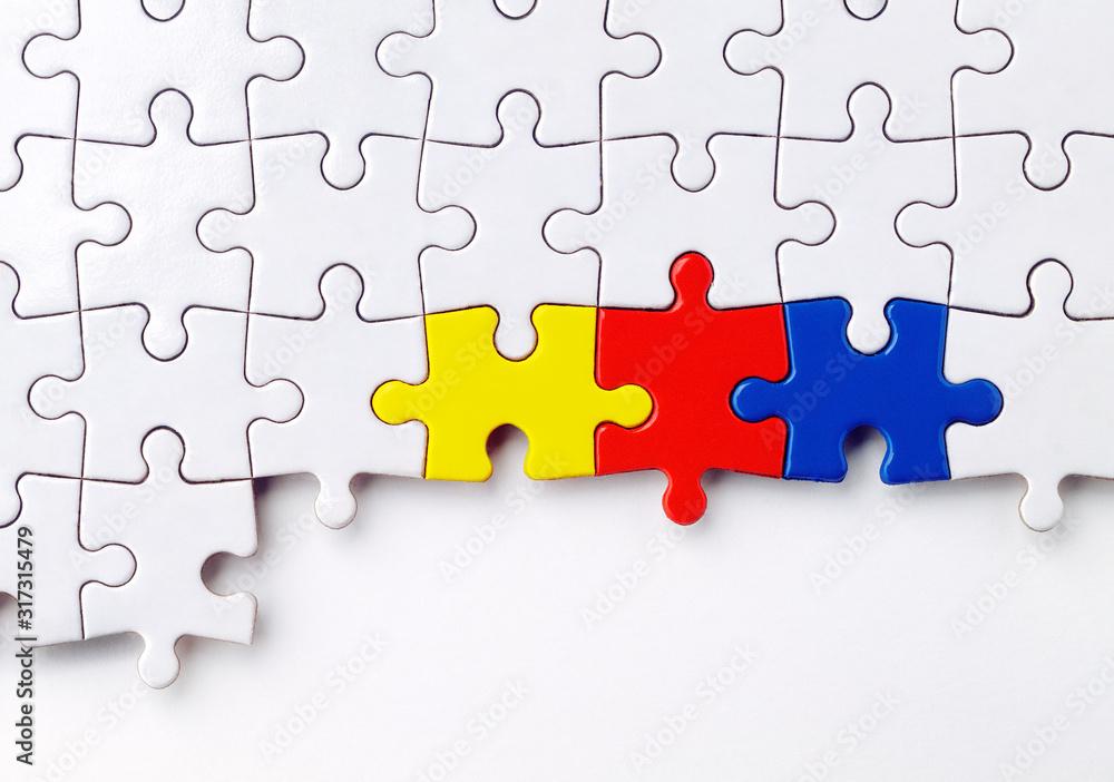 Fototapeta ein weißes Puzzle mit drei farbigen Puzzelteilen