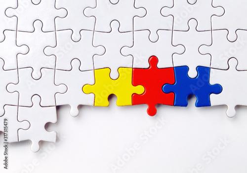 Photo ein weißes Puzzle mit drei farbigen Puzzelteilen