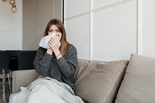 Obraz ill woman blowing nose with tissue sitting on couch at home in apartment - fototapety do salonu
