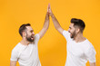 Leinwandbild Motiv Funny young men guys friends in white blank empty t-shirts posing isolated on yellow orange background in studio. People lifestyle concept. Mock up copy space. Giving high five holding hands folded.