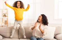 Mother And Daughter Having Fun Jumping On Sofa At Home