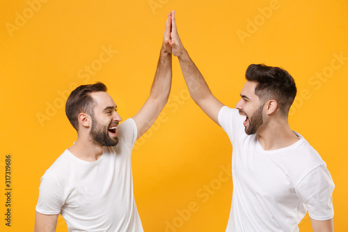 Funny young men guys friends in white blank empty t-shirts posing isolated on yellow orange background in studio Tableau sur Toile