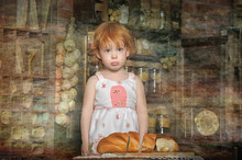 Red-haired Girl In A Light Dress In The Kitchen And A Sliced Loaf Of Bread