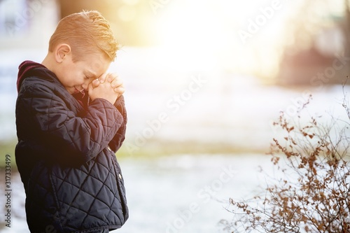 Fototapeta Little boy standing in a park and praying under sunlight with a blurry background obraz