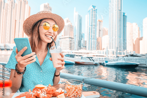 Asian girl has Breakfast with seafood cuisine in a restaurant on the terrace ove Wallpaper Mural