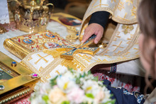 Priest Is Crowning A Young Couple In The Temple. Sacrament Of Marriage. Promise Of Newlyweds In The Church. Hands Of Young Couple Lie On The Scripture And Make Vow, Priest Holds Cross On Their Hands.