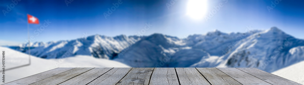 Fototapeta wooden shelf display table top against blue winter mountain panorama and swiss flag snow covered blue mountain layers