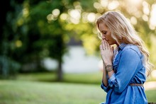 Woman In A Blue Dress Praying In The Garden Under The Sunlight With A Blurry Background