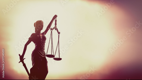Scales of justice set against glowing sky background. Canvas Print
