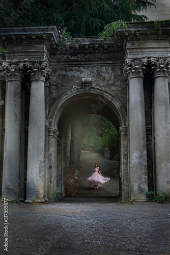 young caucasian girl woman in pink fashion dress outdoors  sunlight nature castle #317355077