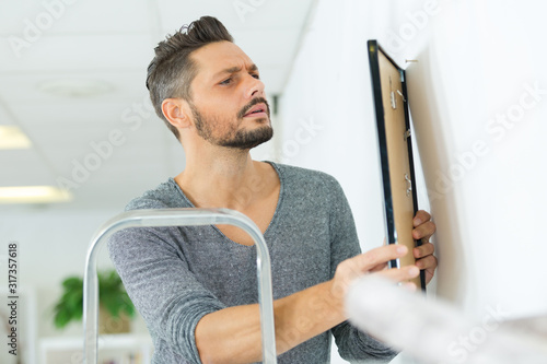 Fotomural male carpenter hanging picture frame on wall at home