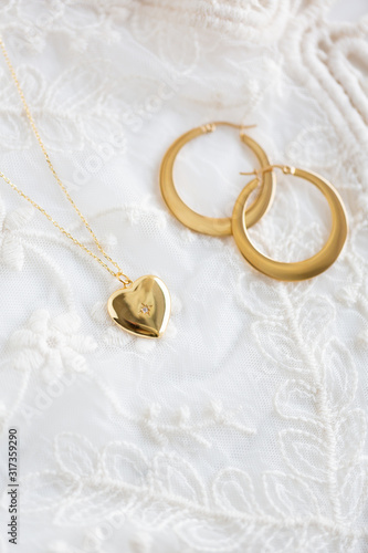 Gold heart necklace and gold hoop earrings on lace Fototapeta