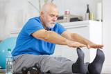 senior man stretching legs indoors