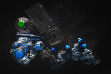 Top View Of Plastic Bottles And Boxes Arranged On Dark Background Surface