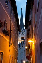 From Below Narrow Street With Bright Lanterns Located Near Church Tower In Calm Aged Town In Evening In Austria