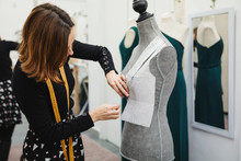 Anonymous Woman With Tape Measure Attaching Paper Cutout To Mannequin With Pin While Making Clothes In Professional Workshop