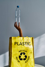 Hand Of Unrecognizable Person Sticking Out From Yellow Bag And Holding Empty Plastic Water Bottle On Gray Background In Studio