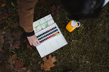 From Above Of Crop Female Artist Taking Box With Watercolor Paints While Spending Time In Autumn Forest With Green Grass And Brown Leaves On Background