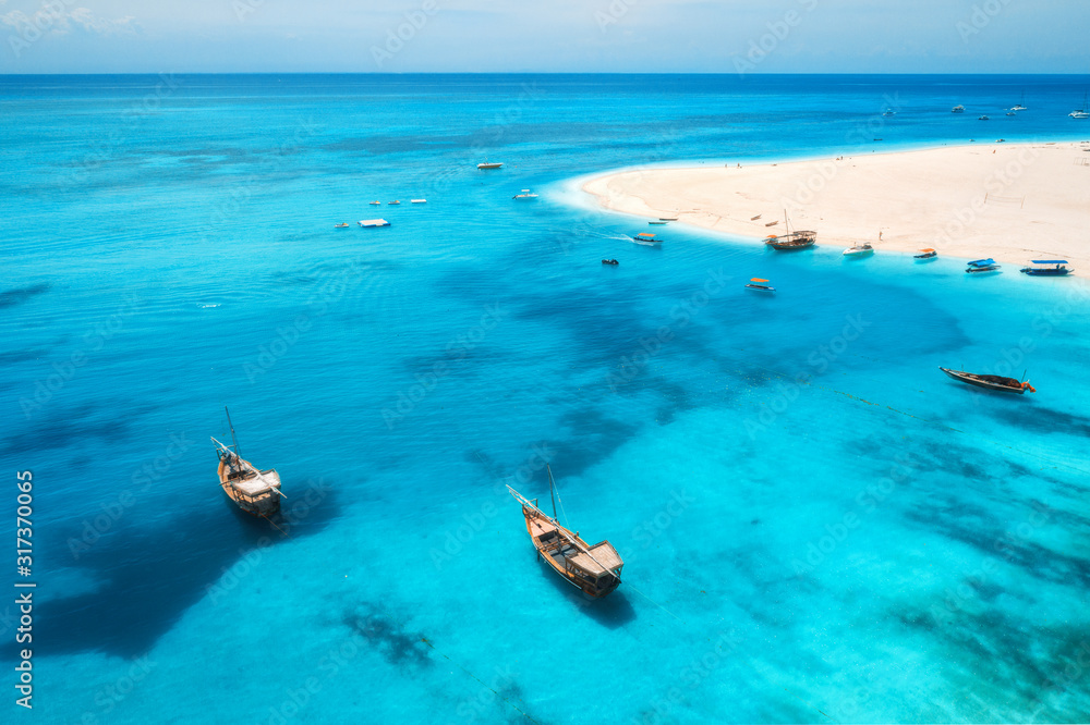 Aerial view of fishing boats on tropical sea coast with transparent blue water and sandy beach at sunny day. Summer holiday. Indian Ocean in Zanzibar, Africa. Landscape with boat, white sand. Top view