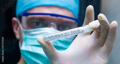 Photo A scientist holds in his hand a test tube with the virus coronavirus