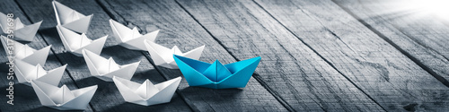 Blue Paper Boat Leading A Fleet Of Small White Boats On Wooden Table With Sunlig Canvas Print