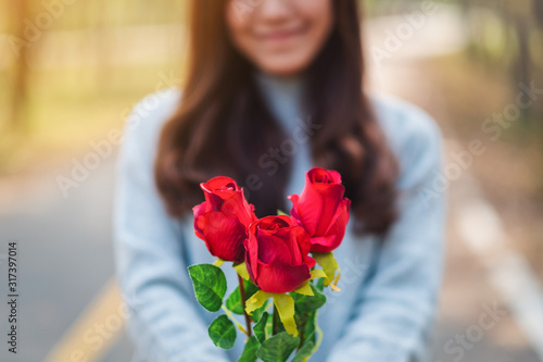 Closeup image of a beautiful asian woman holding and giving red roses flower on Wallpaper Mural