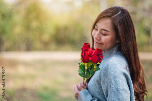 Obraz Closeup image of a beautiful asian woman holding and smelling red roses flower with feeling happy on Valentine's day - fototapety do salonu